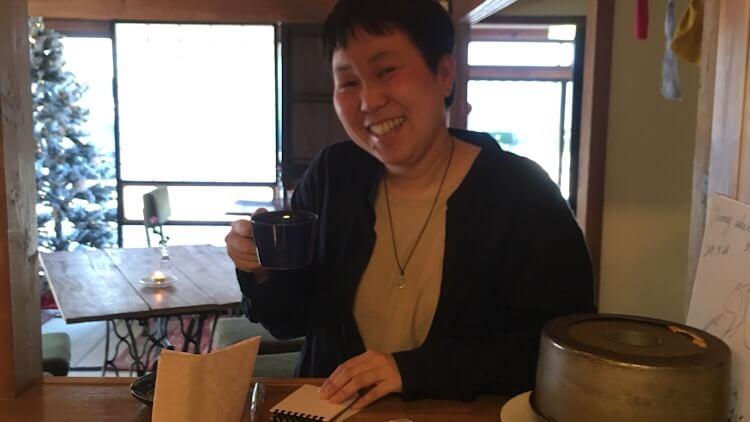 鳥取県米子市両三柳にあるSUNNY-SIDE CAFE(サニーサイドカフェ)向かって左のカウンター席。オーナーに一番近い席。ヒノナナがメモを書いているところ。